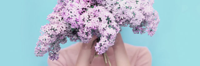 woman hiding her face behind a bouquet of purple flowers
