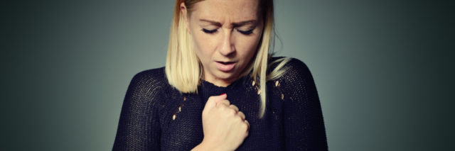 woman with chest pain against plain background