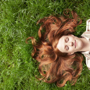 woman with red hair lying in the grass outside