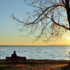 Man Watching the Sunrise over Lake in the Late Fall
