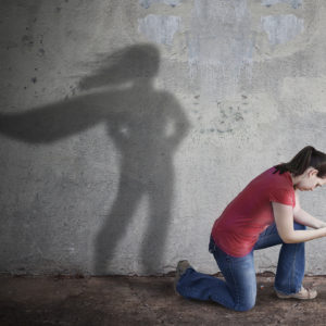 A woman kneeling, with a superhero shadow.