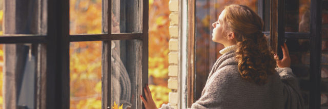woman looking out her window during autumn