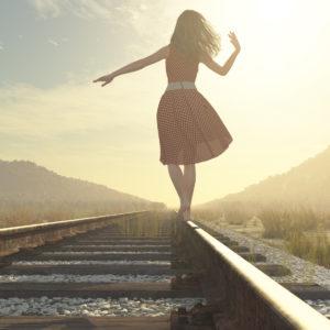 woman walking down a railroad and balancing on the rail