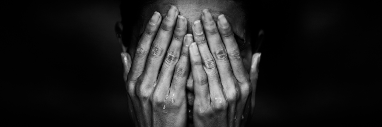 black and white photo of woman holding her face in her hands