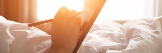 woman with notepad and pen writing in bed in warm sunlight