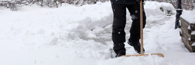 person shovels snow from sidewalk
