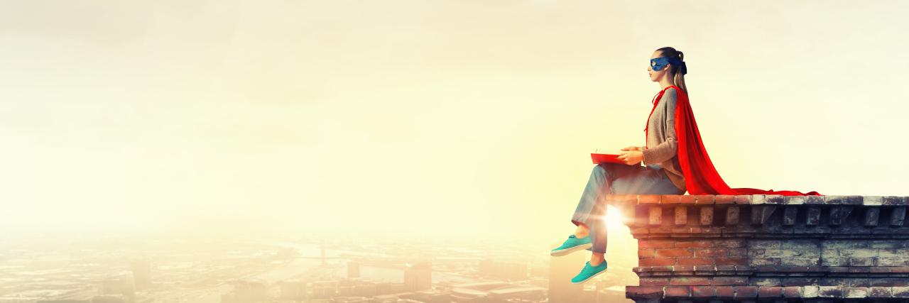 female superhero sitting on edge of building