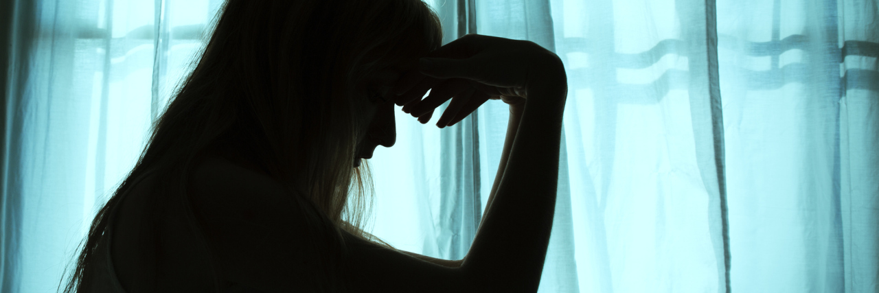 Silhouette of woman sitting in bed holding her head