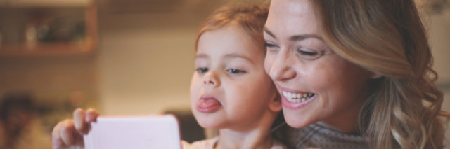 A mom and daughter taking a selfie together, the mom smiling and child sticking her tongue out.