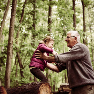 Happy kid playing with grandfather in the park.