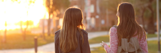 two friends walking outside at sunset
