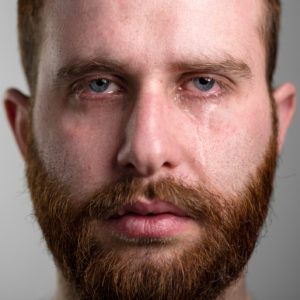 man with beard looking into camera with tears in eyes