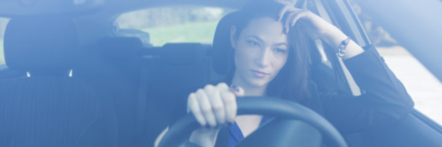 woman driving her car and looking concerned
