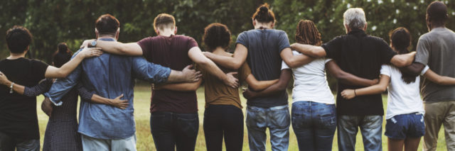 group of friends walking in a line with their arms around each others' shoulders
