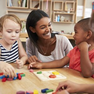 Teacher and students using wooden shapes in montessori school.