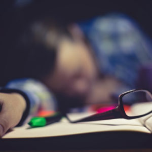 A college student asleep at her desk, camera focusing on her book, glasses, and hand.