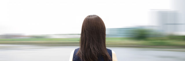 Young woman standing by the river. Blurred background.