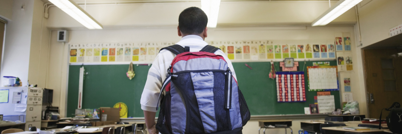 Boy wearing backpack in classroom.