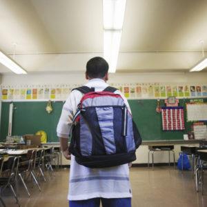 Boy wearing backpack in classroom.