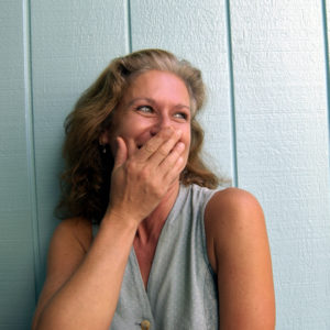 woman standing against a blue wall and laughing