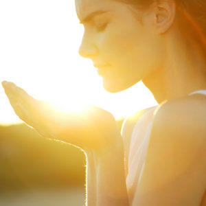 Woman with hands cupped in sunlight.