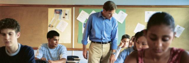 A high school class being taught by a male teacher.