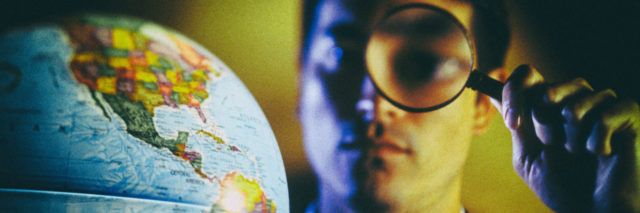Man looking at a globe through a magnifying glass.