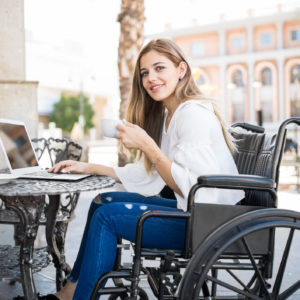 A young woman at a cafe, writing on her laptop, as she sits in her wheelchair.