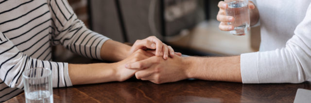 couple holding hands across table