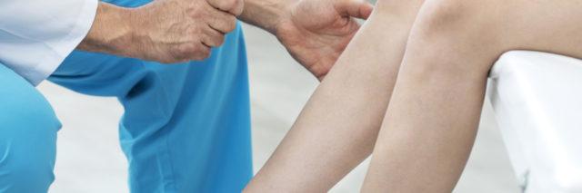 Doctor examining a knee.