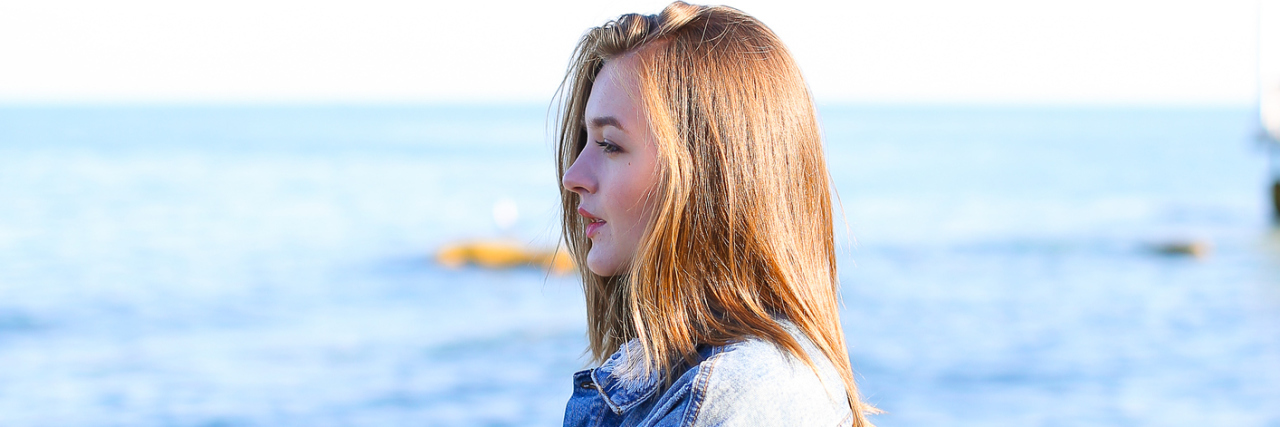 A young woman looking out towards the ocean.