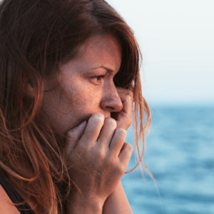 young woman teary alone by sea