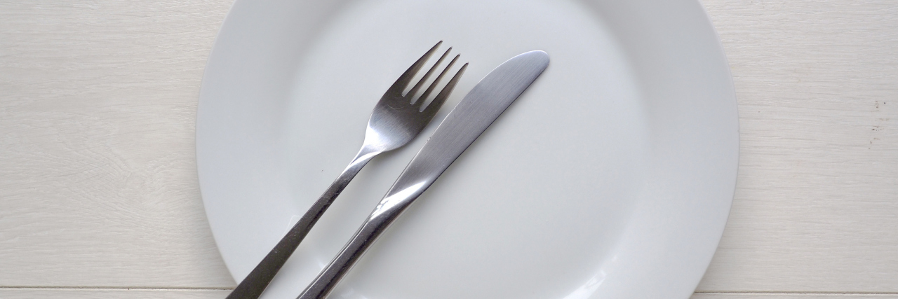 White plate and knife and fork on white wooden background