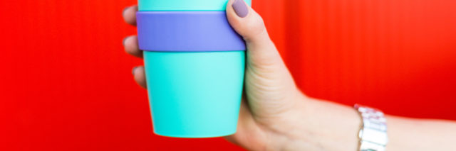 colorful coffee travel mug held against red background by woman