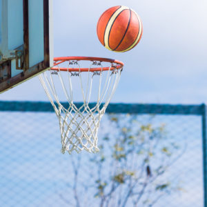 Basketball floating about to get in the hoop at an outdoor basketball court.