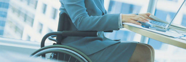 Businesswoman sitting at desk in a wheelchair.
