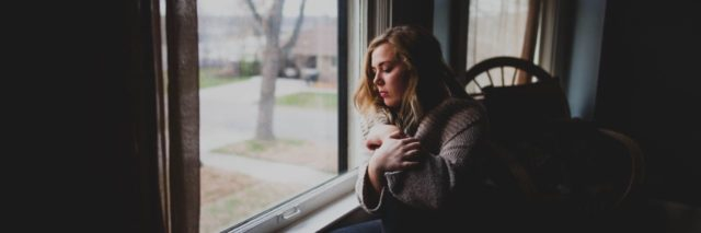girl sitting by window during the fall