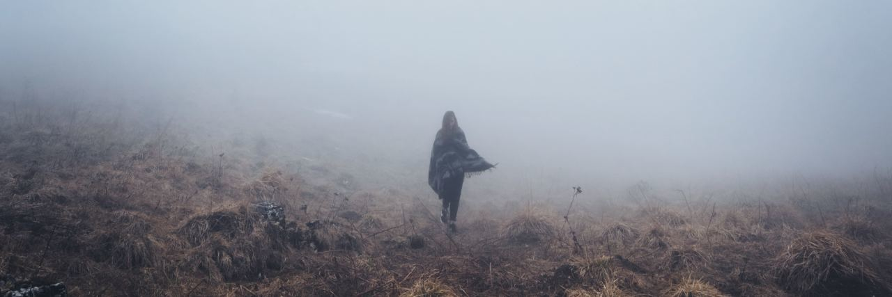 A woman stands in the hills and it is very cloudy