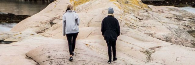 two people walk together on rocks