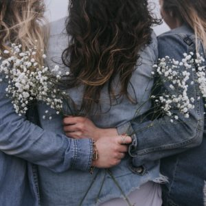 back view of female friends close to each other and holding flowers