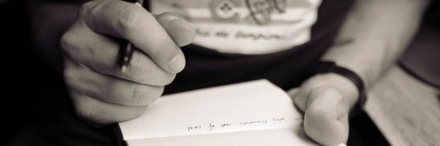 black and white close up of man writing in notepad