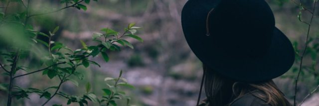 woman in large black hat stands in the woods looking away from the camera