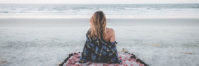woman sitting on a blanket on the beach looking at the ocean