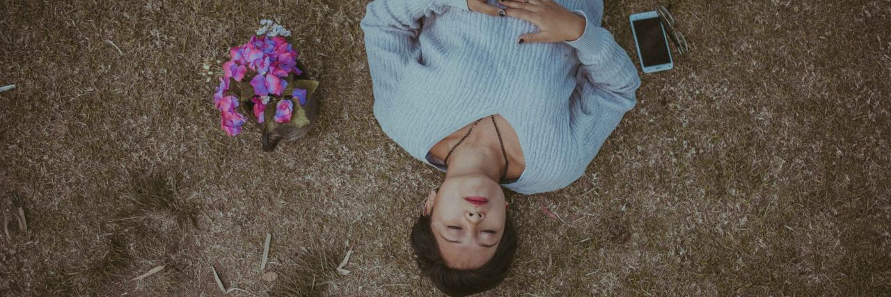 woman lies on the ground with flowers next to her