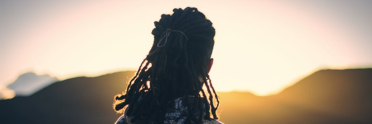 a man with dreadlocks stands on a mountain with a sun setting