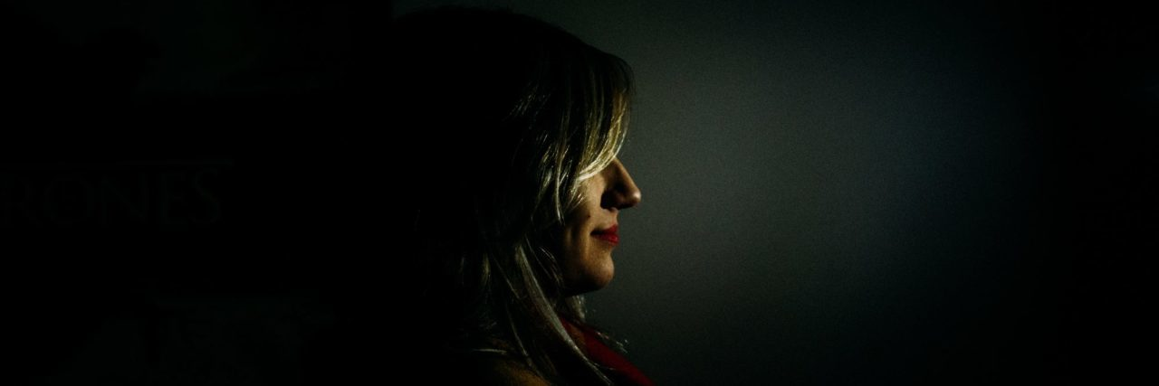 woman partially obscured in darkness with only face visible in profile