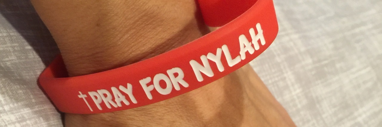 "Red heart bracelet reads, ""Pray for Nylah"""