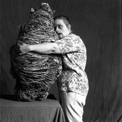 Black and white photo of artist Judith Scott, who has Down syndrome, hugging one of her fiber sculptures.