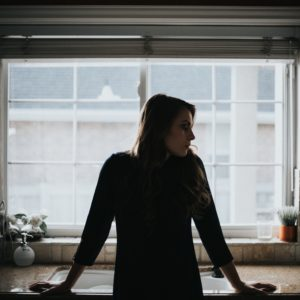 a woman stands in her kitchen looking to the side