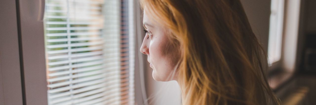 woman with long red hair looks out the window